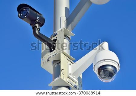 Security camera on blue sky background closeup - stock photo