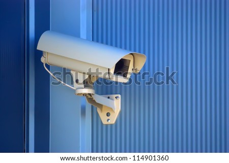 Security camera on the blue wall. - stock photo