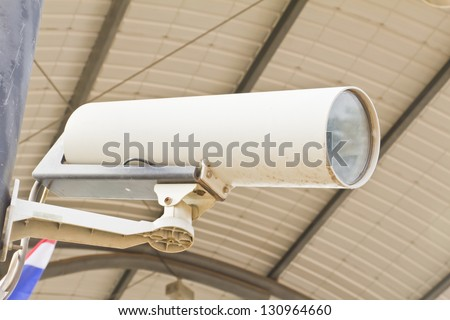Security camera on the post with outdoor housing - stock photo
