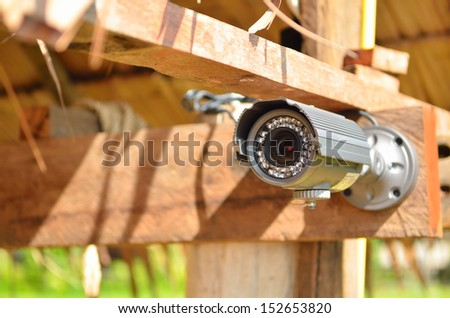 Security camera on the wood wall - stock photo