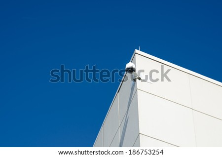 Security Camera on White Building Against Brilliant Blue Sky - stock photo