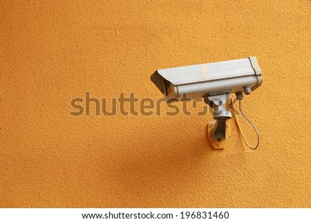 security camera on yellow wall - stock photo