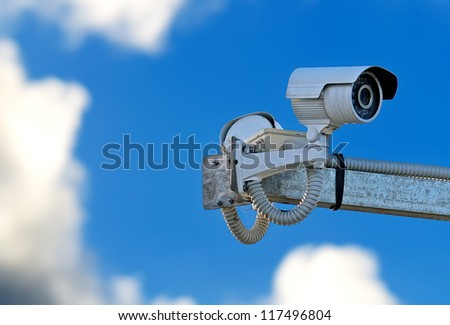 security camera under a cloudy sky - stock photo
