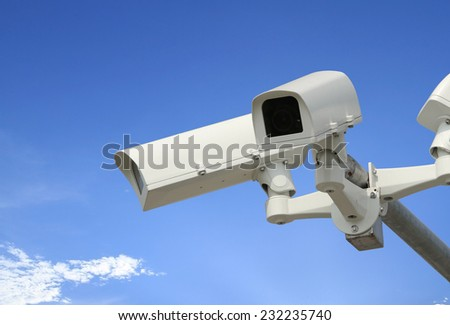 Security camera with blue sky - stock photo