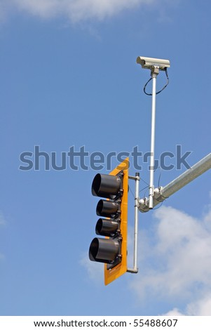 Security camera with traffic light and blue sky background.