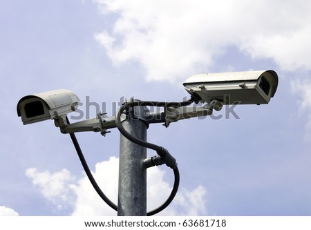 security cameras in front of blue sky - stock photo