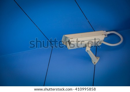 Security CCTV camera in office building background