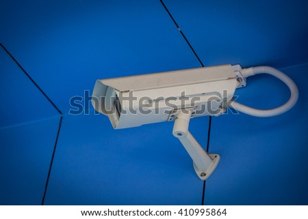 Security CCTV camera in office building background - stock photo