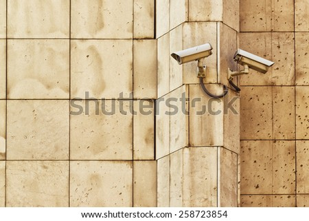 Security CCTV camera mounted on the building wall as apart of private property protection system or Big Brother Concept - stock photo