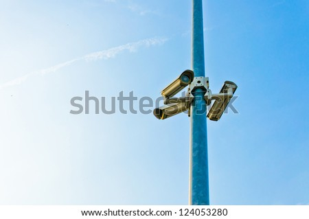 security cctv cameras on a pole with blue sky background - stock photo