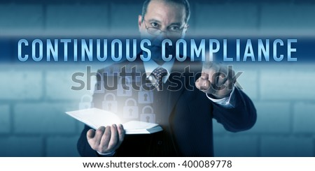 Security director or CISO is touching CONTINUOUS COMPLIANCE on a visual interactive screen. Business metaphor and information technology concept for best practice workflow and audit-readiness. - stock photo