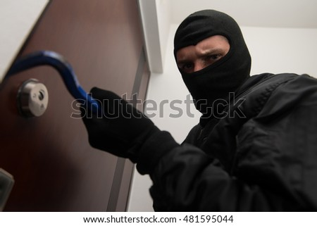 Security - Disguised Burglar Breaking In An Apartment Or Office To Steal Something