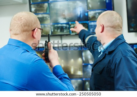security executive chief discussing activity with worker in front of video monitoring surveillance security system - stock photo