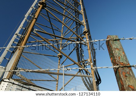 Security fence around a communications relay tower to prevent copper cable theft - stock photo