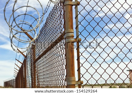 Security fence is old and rusty that surrounds the property.  - stock photo