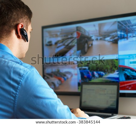 Security guard monitoring video in security room. - stock photo