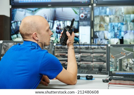 security guard watching video monitoring surveillance security system with portable radio transmitter - stock photo