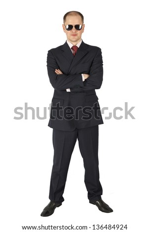 Security guard wearing a suit and sunglasses isolated on white background - stock photo
