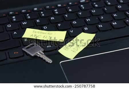 Security key and two easy, weak passwords on the sticky notes, located on laptop keyboard. - stock photo