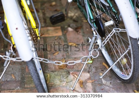 Security lock blocking the bicycle wheel in park - stock photo