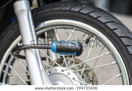 Security lock blocking the motorcycle wheel - stock photo