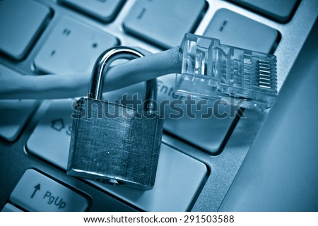 security lock with lan wire on computer keyboard - stock photo