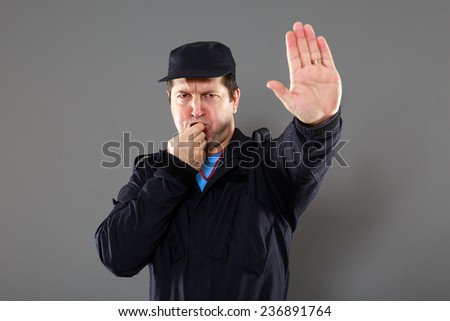 security officer making the stop sign. grey background - stock photo