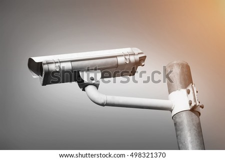 Security or CCTV  camera mounted on a steel pole on gray background