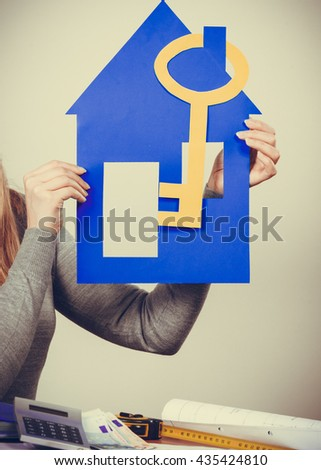 Security safety home ownership concept. Young blonde lady holding symbols. Cheerful girl showing house key cutouts. - stock photo