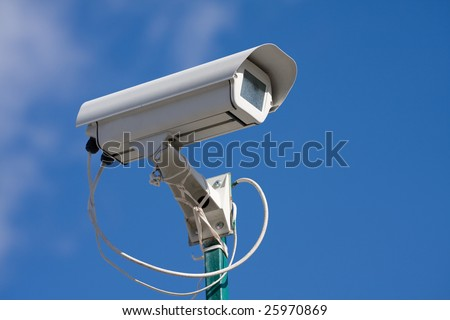 security video camera on background blue sky