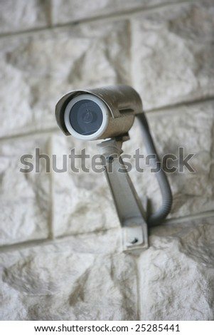 security video camera on the wall - stock photo