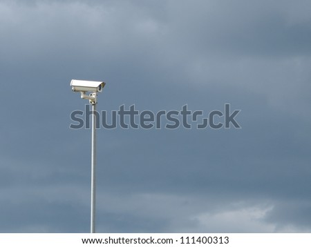 Security video surveillance camera on stormy sky background