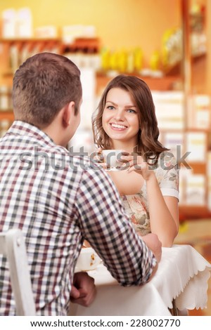 Seducing beautiful woman looking at her lover with coffee cup. Having romantic talk - stock photo
