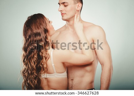 Seductive alluring passionate young couple lovers embracing in studio. Handsome muscled half naked semi nude man and woman in lingerie. Love and passion.