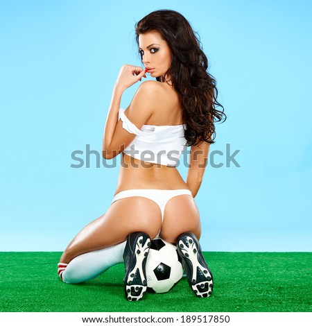 Seductive beautiful curvaceous female soccer player in an erotic pose sitting on a soccer ball in her lingerie showing her shapely buttocks and looking back with a beguiling sultry look