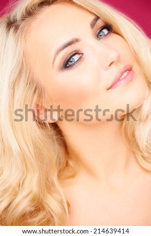 Seductive beautiful young blond woman with her head tilted back looking sideways at the camera - stock photo