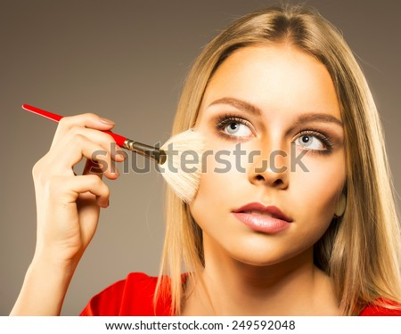 seductive blond woman doing make up - stock photo