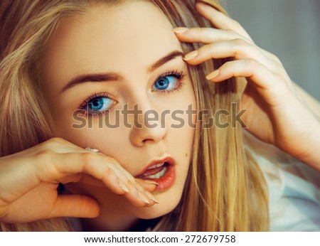 Seductive blonde woman with blue eyes looking at camera. Studio shot - stock photo