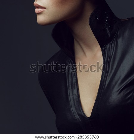 Seductive decollete concept. Portrait of beautiful young woman. Perfect natural make-up. Black leather dress with collar. Healthy skin. Close up. Copy-space. Studio shot - stock photo