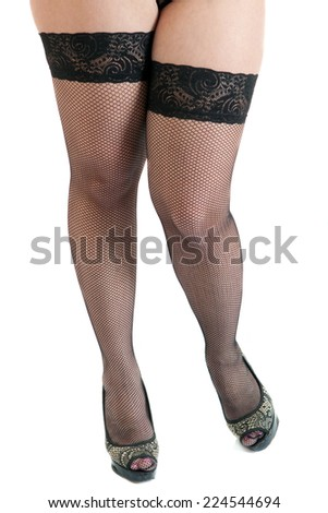 Seductive female legs wearing black stockings and high heels - stock photo