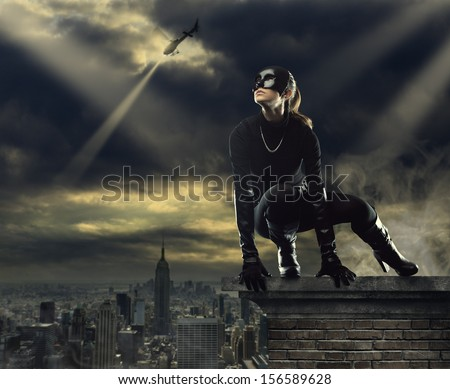 Seductive Female thief running away over the rooftops - stock photo