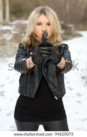 Seductive girl aiming with a gun against the snow - stock photo