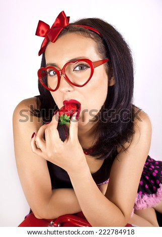Seductive girl in glasses with strawberries - stock photo