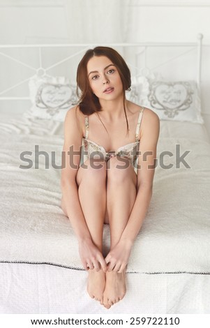 seductive girl sitting on white bed hugging her legs hands - stock photo