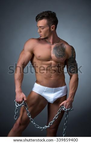 Seductive male model with perfect tattooed body - stock photo