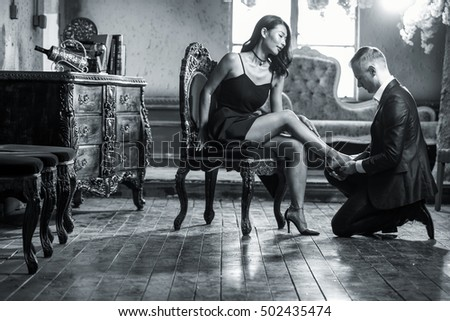 Seductive man playing with his wife's legs and shoes before they go to the bedroom