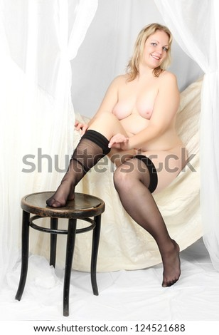 Seductive overweight woman in bedroom. Vintage style studio shot. Great for calendar. - stock photo