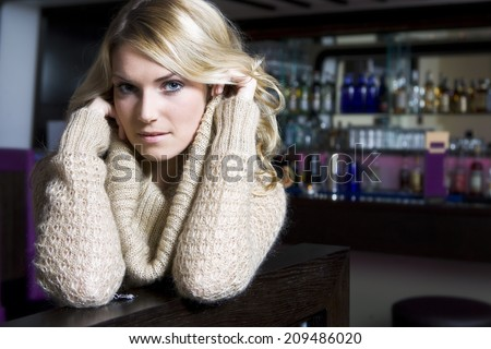 Seductive Pretty Woman in a Bar Wearing Fashioned Knit Jacket, Looking at Camera - stock photo