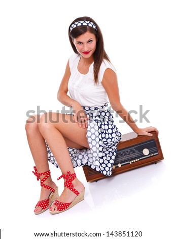 Seductive retro woman sitting on a retro radio, showing her legs in provocative way. Isolated.