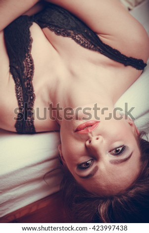 Seductive sexy gorgeous woman wearing lingerie in bed at home. Attractive sensual young girl with long hair. Female underwear fashion. - stock photo